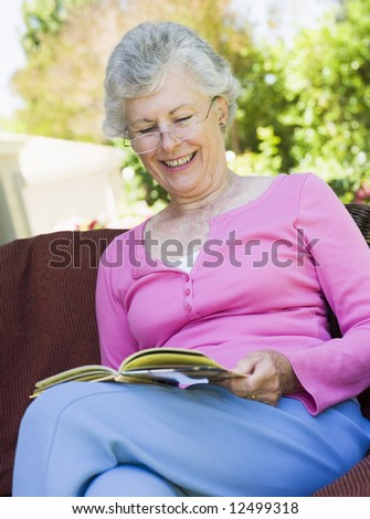 Senior woman sitting on garden seat reading book - stock photo