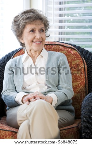 Senior woman sitting on living room chair smiling - stock photo