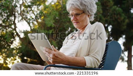 Senior woman sitting with tablet at the park - stock photo