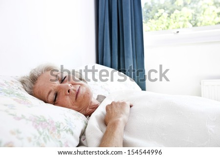 Senior woman sleeping in bedroom at home - stock photo