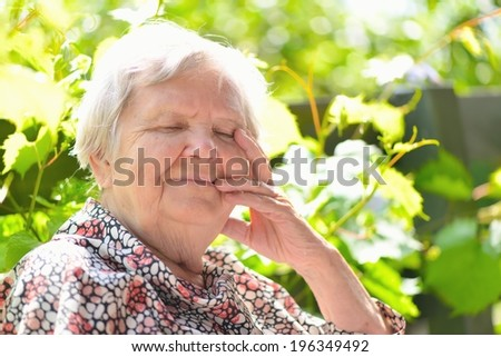 Senior woman smiling and dreaming in garden. MANY OTHER PHOTOS FROM THIS SERIES IN MY PORTFOLIO. - stock photo