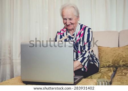 Senior woman smiling and using laptop - stock photo