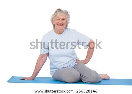 Senior woman smiling on exercise mat on white background - stock photo