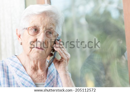 Senior woman speaking on mobile phone - stock photo