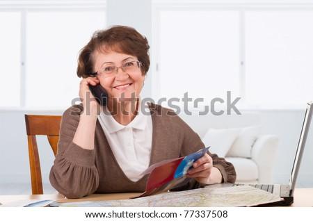 senior woman speaking on phone choosing vacations - stock photo