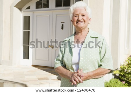 Senior woman standing outside front door of house - stock photo