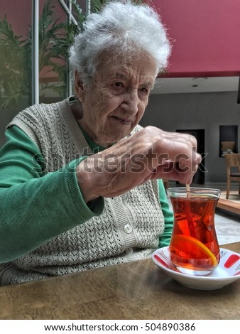 senior woman stirring a glass of tea on table