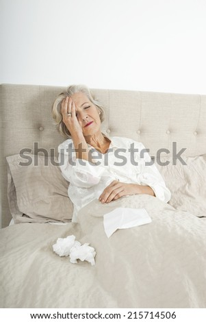 Senior woman suffering from headache resting in bed - stock photo