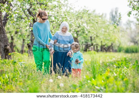 Senior woman supported by granddaughter and great grandson walking in blossoming orchard - stock photo