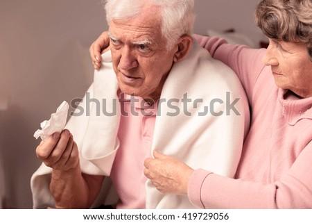 Senior woman supporting her ill, sad husband - stock photo