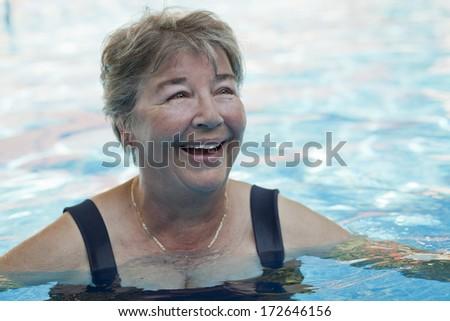 Senior woman swimming in a pool - stock photo