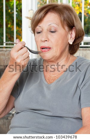 Senior woman taking medicine with spoon