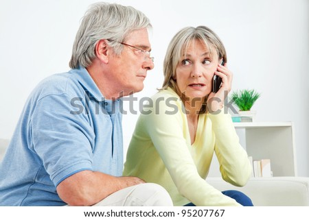 Senior woman talking on cell phone at home in living room - stock photo