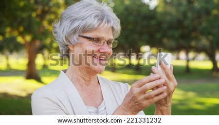 Senior woman texting on smartphone at the park - stock photo