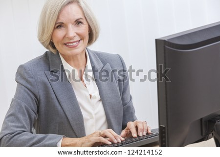 Senior woman typing using a computer at home or in an office - stock photo