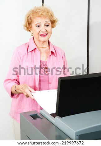 Senior woman using a new optical scanner voting machine to cast her ballot.   - stock photo