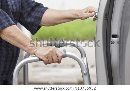 senior woman using a walker at car park - stock photo