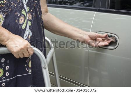 senior woman using a walker at car park - stock photo