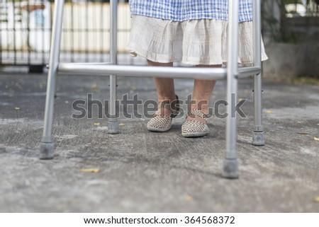 senior woman using a walker at home - stock photo