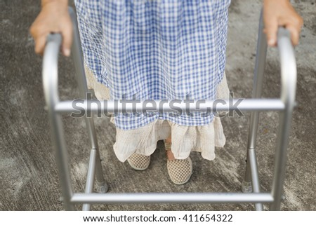 senior woman using a walker on walk way.  (focus at dress) - stock photo