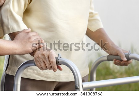 senior woman using a walker with caregiver - stock photo