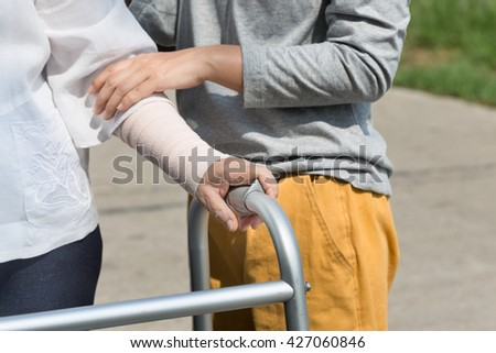 senior woman using a walker with caregiver on street. - stock photo