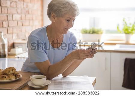 Senior woman using her mobile phone  - stock photo