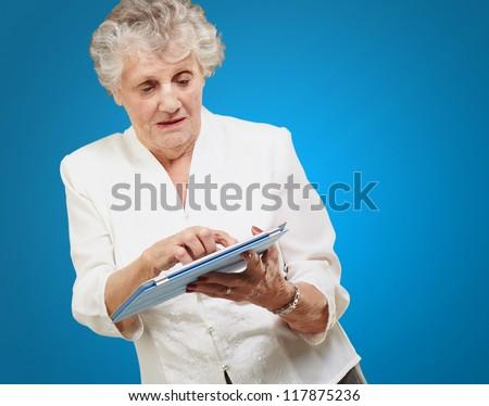 Senior woman using ipad isolated on blue background - stock photo