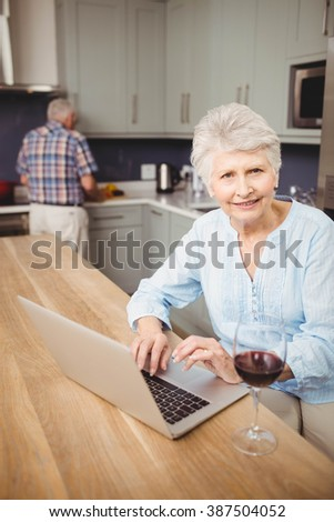 Senior woman using laptop and man working in kitchen at home - stock photo