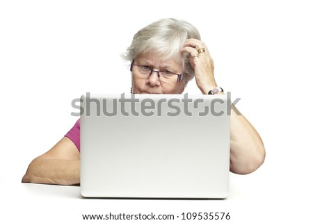 Senior woman using laptop whilst looking confused on white background - stock photo