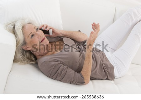 Senior Woman Using Phone At Home lying on sofa - stock photo