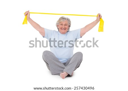 Senior woman using resistance band on white background - stock photo