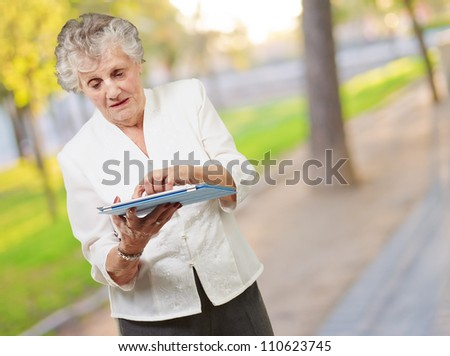 Senior woman using tablet, outdoor