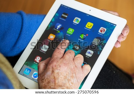 Senior woman using tablet with many app on a ipad screen - stock photo