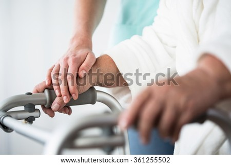 Senior woman using walking frame and helpful hand - stock photo