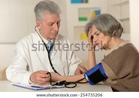 Senior woman visiting doctor at hospital - stock photo