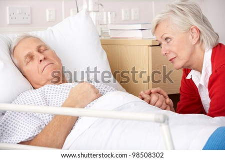 Senior woman visiting husband in hospital - stock photo