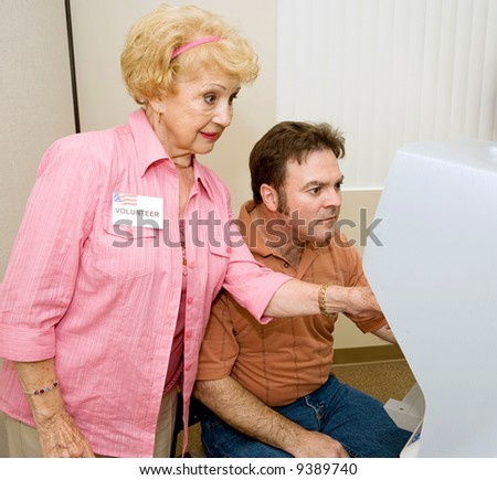 Senior woman volunteer explaining new voting machine to voter. - stock photo