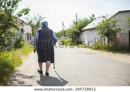 Senior woman walking down street in countryside  - stock photo
