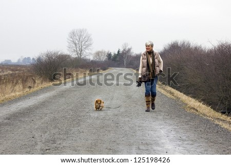 Senior woman walking her dog on an overcast winter day. - stock photo
