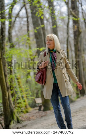 Senior woman walking in a park - stock photo