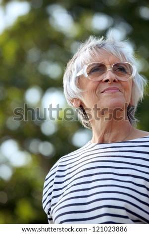 senior woman walking in the park - stock photo
