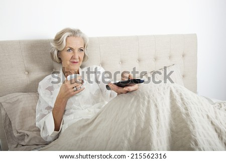 Senior woman watching TV while having coffee in bed - stock photo
