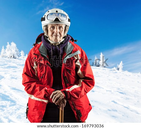 Senior woman wearing ski jacket and goggles on snowy slope in mountains. With clipping path. - stock photo
