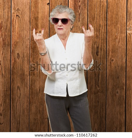Senior woman wearing sunglasses doing funky action, indoor - stock photo