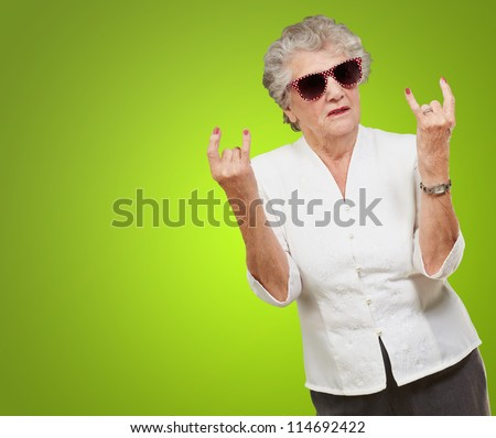Senior woman wearing sunglasses doing funky action isolated on green background - stock photo