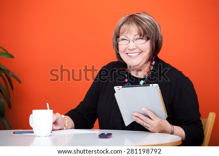 senior woman with a tablet and notes - stock photo