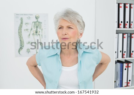 Senior woman with back pain standing in the medical office - stock photo