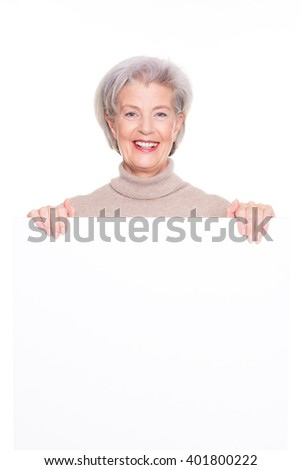 Senior woman with blank sign in front of white background - stock photo