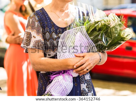 Senior woman with bouquet of flowers - stock photo
